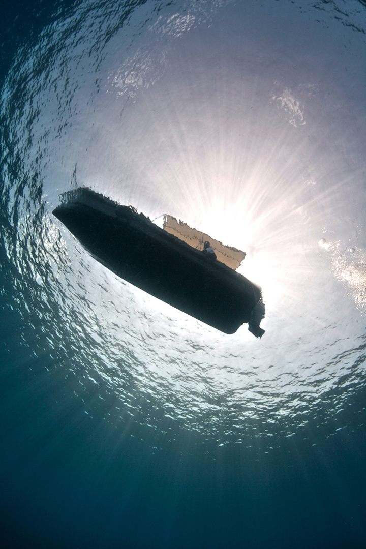 A sillhouette of a dive boat from under water.